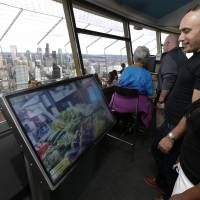 Tourists check out a virtual reality display that lets visitors explore Pike Place Market and other attractions atop the Space Needle in Seattle. | AP