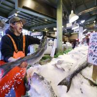 Playing catch: A fishmonger tosses a salmon at Pike Place Fish Market in Seattle. | AP