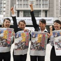Four cheers: Government workers hold up copies of a newspaper announcing the decision in 2013 to award the 2020 Olympics to Tokyo. Japan's four main newspapers have announced they will be official sponsors for the games, but other publications believe this could affect objective reporting of the event. | YOSHIAKI MIURA