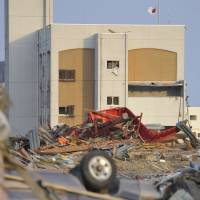 Rebuilding: A police station in Minamisanriku, Miyagi Prefecture, sits amid debris following the Great East Japan Earthquake of March 11, 2011. The area is now under reconstruction. | KYODO