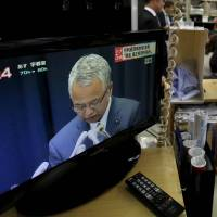 Money matters: A TV broadcasts a news conference in which economy minister Akira Amari announced his resignation. | REUTERS