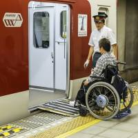 Help on hand: A station attendant in Kyoto helps a person in a wheelchair board a train. | ISTOCK