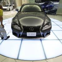 Losing their sheen: A visitor looks at a Toyota Lexus sedan at the company's showroom in Nagoya. Even domestic automakers seem to be concentrating on expanding overseas as the market at home looks bleak. | BLOOMBERG