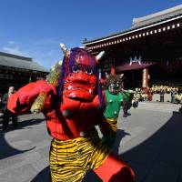 Two parents of kindergarten students dress up as demons, while the children throw beans to ward away evil spirits and bring good luck, as part of the annual Setsubun Festival at Sensoji Temple in Tokyo on Wednesday. | AFP-JIJI