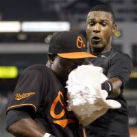 The Orioles' Adam Jones hits teammate Felix Pie in the face with a pie in an Aug. 14, 2009, file photo. | AP