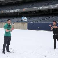 New Zealand's Ryan Crotty (right) tosses a rugby football to Ireland's Tommy Bowe on Tuesday at Soldier Field in Chicago. | AP