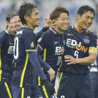 Sanfrecce Hiroshima's Takuma Asano (10) is congratulated by teammates after scoring on a penalty kick against Gamba Osaka in the second half on Saturday in the Fuji Xerox Super Cup in Yokohama. | KYODO