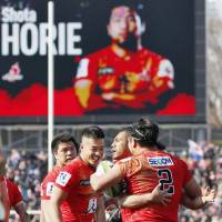 Teammates congratulate Sunwolves capatain Shota Horie (2) after he scores the first try in the team's first Super Rugby match on Saturday. | KYODO