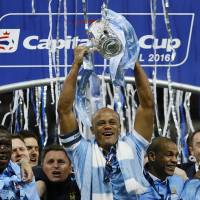 Manchester City captain Vincent Kompany raises the trophy after his team's victory over Liverpool in the League Cup final on Sunday at Wembley Stadium in London. | AP