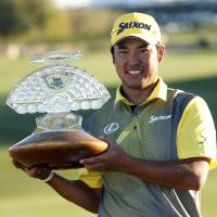 Hideki Matsuyama holds the trophy after winning the Phoenix Open on Sunday. | AP