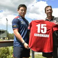 Ayumu Goromaru (left) poses with Queensland Reds coach Richard Graham after being unveiled by the Super Rugby team on Monday. | KYODO