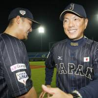 Japan manager Hiroki Kokubo (right) shares a laugh with Sho Nakata during the Premier 12 on Nov. 12, 2015. | KYODO