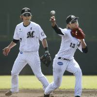 Lotte infielder Taiga Hirasawa makes a throw as Daichi Suzuki watches during practice last week. | KYODO