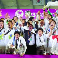 Makoto Teguramori lifts the trophy after Japan's victory in the Under-23 Asian Championship on Jan. 30, in Doha.   AFP-JIJI
