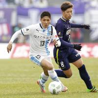 Kawasaki Frontale's Yoshito Okubo (left) moves the ball in front of Sanfrecce Hiroshima's Kazuyuki Morisaki in their J. League season opener on Saturday afternoon at Edion Stadium. Frontale won 1-0. | KYODO