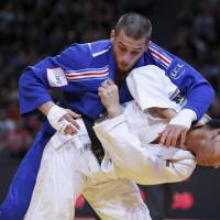 Daiki Nishiyama (bottom) competes with France's Alexandre Iddir in the men's 90-kg final at the Judo Grand Slam in Paris on Sunday. | REUTERS