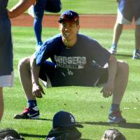 Pitcher Kenta Maeda stretches during his first workout with the Los Angeles Dodgers in Glendale, Arizona, on Monday. | KYODO