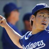 Dodgers right-hander Kenta Maeda tosses a  pitch during Friday's workout in Glendale, Arizona. | AP