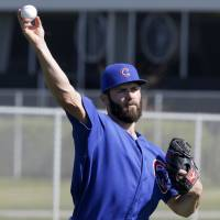 The Cubs' Jake Arrieta throws a ball during a practice session on Saturday in Mesa, Arizona. | AP