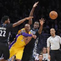 Los Angeles' Kobe Bryant (center) passes the ball during the Lakers' 119-115 win over the Timberwolves on Tuesday. | AP
