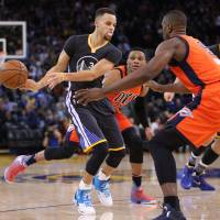 Warriors guard Stephen Curry passes around the Thunder's Serge Ibaka during their game on Saturday. Golden State won 116-108. | USA TODAY / REUTERS