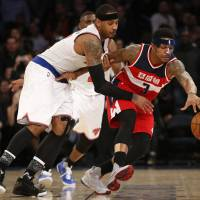 New York's Carmelo Anthony (left) defends Washington's Bradley Beal during their game on Tuesday. | AP
