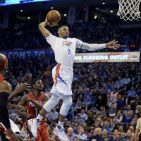 Thunder guard Russell Westbrook (right) goes up for a dunk during Oklahoma City's win on Thursday. | USA TODAY / REUTERS