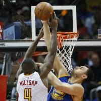 Golden State's Andrew Bogut blocks a shot by Atlanta's Paul Millsap in the second half on Monday night. The Warriors beat the Hawks 102-92. | AP