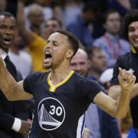 Warriors guard Stephen Curry celebrates after his shot in the final seconds of overtime during Golden State's 121-118 win over the Oklahoma City Thunder on Saturday. | AP