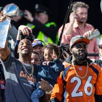 Broncos cornerback Aqib Talib (left) lifts the Vince Lombardi Trophy alongside safety Darian Stewart at a Super Bowl 50 victory parade in Denver on Tuesday. | USA TODAY / REUTERS