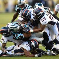 Members of the Broncos defense tackle the Panthers' Fozzy Whittaker (43) during Super Bowl 50 on Sunday in Santa Clara, California. | AFP-JIJI