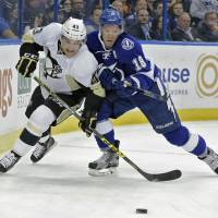 Pittsburgh's Conor Sheary (left) vies for the puck with Tampa Bay's Ondrej Palat in the first period on Friday. The Lightning downed the Penguins 6-3. | AP