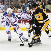 Pittsburgh's Derrick Pouliot (right) battles for the puck with New York's J.T. Miller on Wednesday. | AP