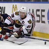 Chicago's Jonathan Toews (right) falls to the ice while battling for the puck with New York's Keith Yandle on Wednesday night. | AP