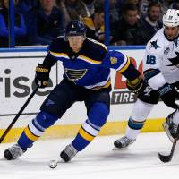 St. Louis' Carl Gunnarsson clears the puck as San Jose's Mike Brown pursues in the first period Monday night. | AP