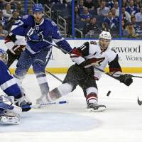 Arizona's Martin Hanzal (center) looks for a rebound against the Tampa Bay defense during the Lightning's 2-1 win on Tuesday. | AP