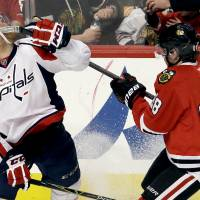 Capitals defenseman Karl Anzar (left) is hit by a high stick from Blackhawks right wing Patrick Kane on Sunday in Chicago. | AP