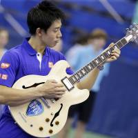 Kei Nishikori plays the guitar he was given as a reward following his victory over Taylor Fritz in the Memphis Open final on Sunday. | AP
