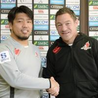 Sunwolves coach Mark Hammett (right) shakes hands with newly announced team captain Shota Horie on Tuesday. | KYODO