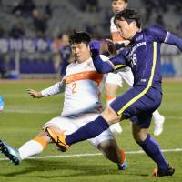 Sanfrecce Hiroshima's Kohei Shimizu (right) crosses the ball during last week's Asian Champions League game against China's Shandong Luneng. | KYODO