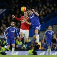 Manchester United's Wayne Rooney (left) and Chelsea's Cesar Azpilicueta compete for the ball during their match at Stamford Bridge on Sunday in London. | AP