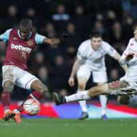 West Ham's Enner Valencia (left) shoots as Liverpool's Lucas Leiva tries to block during their F.A. Cup game on Tuesday.   REUTERS