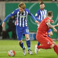 Hertha Berlin's Genki Haraguchi (left) takes on the Heidenheim defense during their German Cup game on Wednesday. | KYODO