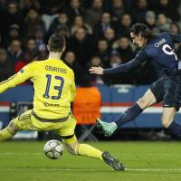 Paris St. Germain's Edinson Cavani shoots past Chelsea goalkeeper Thibaut Courtois during their match on Tuesday in Paris. PSG won the Champions League first-leg match 2-1. | REUTERS