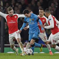 Barcelona's Lionel Messi (center) takes on the Arsenal defense at Emirates Stadium in London on Tuesday. | REUTERS