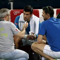 Novak Djokovic receives treatment before withdrawing from his quarterfinal match against Feliciano Lopez of Spain at the Dubai Tennis Championships on Thursday. | REUTERS