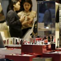 Women try out lipsticks at a Shiseido Co. outlet in Tokyo on Monday. A survey found economists are rating Abenomics poorly, citing a lack of structural reform, including getting more women into the workforce. | REUTERS