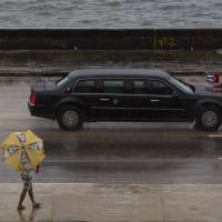 The limo carrying President Barack Obama drives along the Malecon seawall on its way to Old Havana Sunday. Obama gave Airbnb the green light to open up business in Cuba, offering one-stop accommodation shopping. | AP