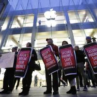 Protesters carry placards outside an Apple store Feb. 23 in Boston. Tech companies, security experts and civil liberties groups are filing court briefs supporting Apple in its battle with the FBI. The groups oppose a judge's order that would require Apple to help federal agents hack an encrypted iPhone used by a San Bernardino mass shooter. | AP