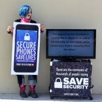 Activist Aki Rose holds a placard reading 'Secure Phones Saves Lives' while protesting in front of the U.S. District Court in Riverside, California, on March 22. | AFP-JIJI